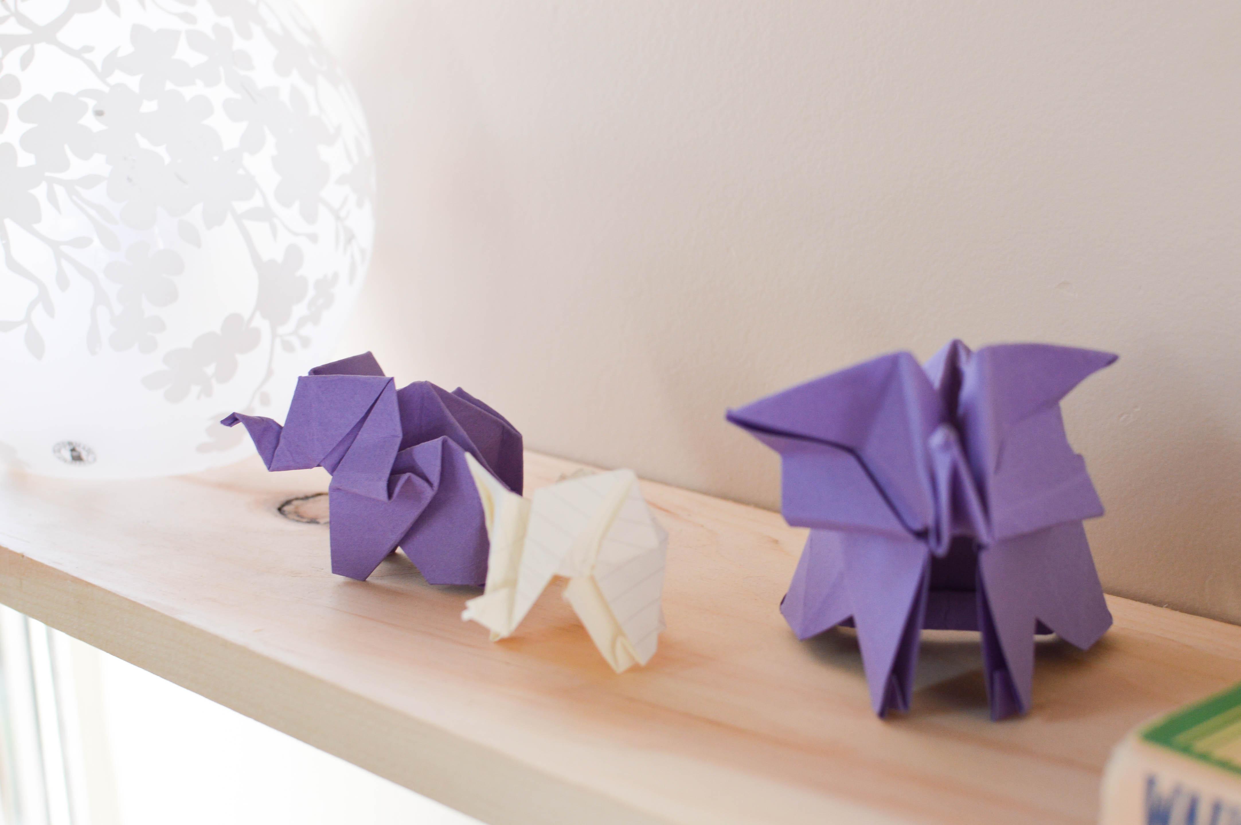 Origami elephants sit on a wooden shelf